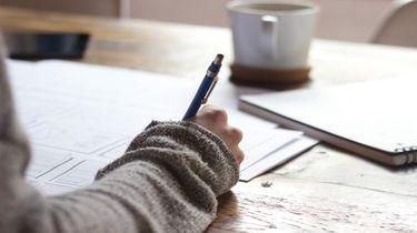 Een leerling van een middelbare school die schrijft