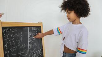 tafels leren / kind rekent op een schoolbord