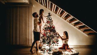 Een gezin dat samen de kerstboom optuigt