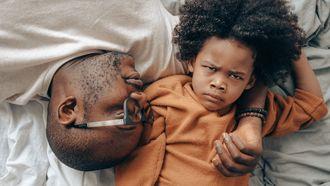 Vader die zijn kind straf geeft waardoor het kind boos kijkt