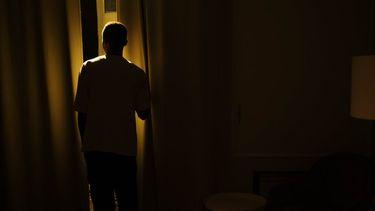 tiener / jongen kijkt naar buiten door gordijnen