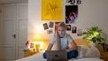 Tiener op bed met laptop ervaart stress
