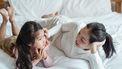 Moeder die met haar kind op bed ligt en praat over heftige nieuwsberichten