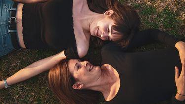 moeder en dochter liggen samen in het gras