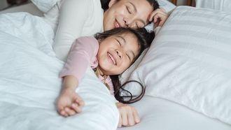 Moeder die haar dochter knuffelt in bed