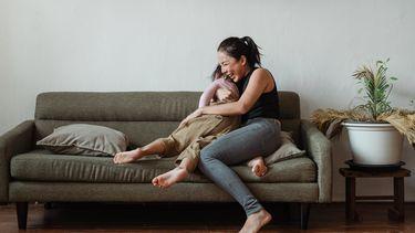 Vrouw knuffelt haar zoon op de bank en heeft een-op-een tijd