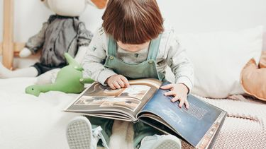 spraak bevorderen / kind leest een boek op bed