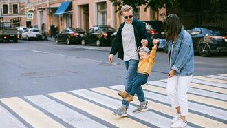 grote stad / ouders lopen met kind op het zebrapad