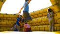 Kinderen die springen in een luchtkasteel op een kinderfeestje