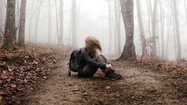 weglopen / meisje zit alleen in het bos op de grond
