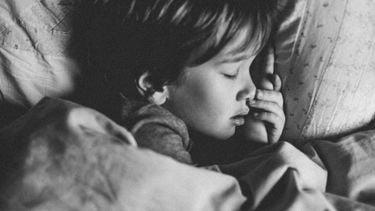 Jongetje dat in bed ligt en slaapt