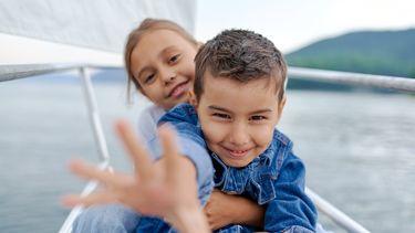 Gelukkige kinderen krijgen. Jongetje en meisje op boot