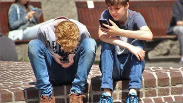 Twee pubers op een stoepje, starend naar een beeldscherm