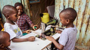 opvoedgewoontes / Keniaans gezin zit om naaimachine heen