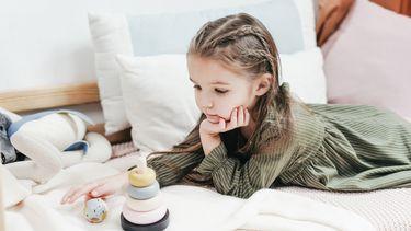 wendagen / meisje ligt op bed en kijkt beteuterd