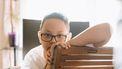 Jongen die over de rugleuning van de stoel kijkt en verdrietig is om de scheiding van zijn ouders
