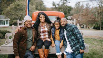 Moeder met haar gezin die voor een auto poseren