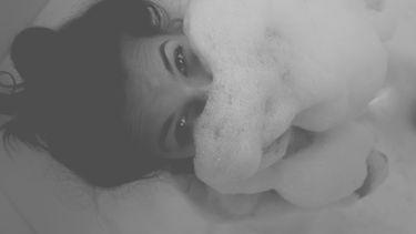 vrouw ligt ontspannen in bad met sop