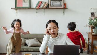 geduld / moeder aan tafel met laptop met kinderen op achtergrond