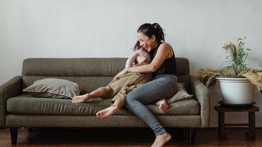 Moeder die hoogsensitief is en met haar dochter knuffelt op de bank