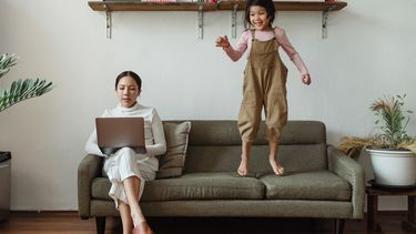 Moeder die op de bank zit te werken met een druk kind dat op de bank springt