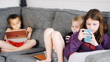 schermtijd / kinderen op de bank op telefoon en tablet