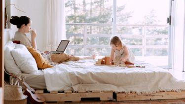 thuis werken / moeder en kind op bed