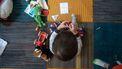 Een peuter met zijn speelgoed om zich heen die moet leren delen