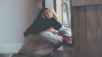 Meisje dat uit het raam kijkt en zich schaamt voor haar seksualiteit