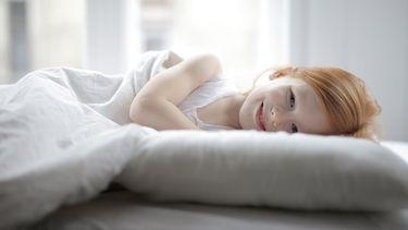 overprikkeld kind ligt in bed