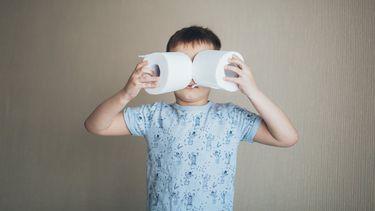 verstopping / jongetje houdt twee toiletrollen voor gezicht