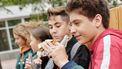 Jongens die een boterham eten, maar waarvan er een een pinda-allergie heeft
