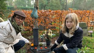 dood / vrouw en kind knielen naast graf