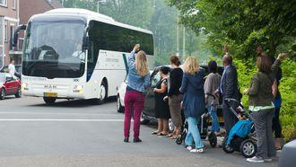 Kinderen zwaaien bus uit voor uitje