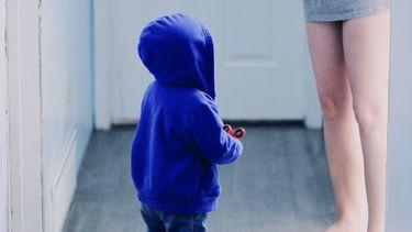 autoritair opvoeden / kind met blauw vest staat in de gang