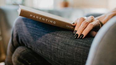 vrouw met boek over opvoeden op schoot