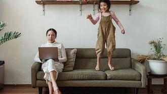 hyperactiviteit / werkende moeder met springend kind op bank