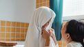 Moeder die haar dochter afdroogt nadat ze uit de douche is gekomen