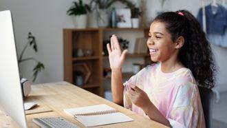 lessen / meisje zwaait naar webcam op computer