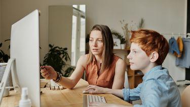 Moeder die haar zoon helpt bij het huiswerk en daar later grappige tweets over schrijft naar ouders