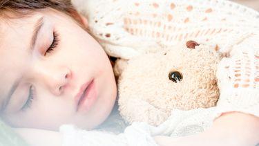 Kind met koorts dat in bed ligt