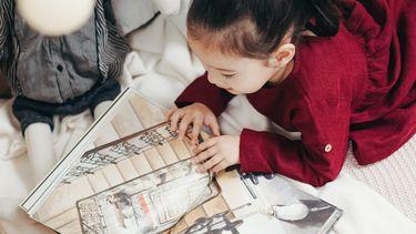 leesniveau / meisje leest boek op bed