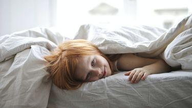 Kind dat in bed ligt en moeilijk in slaap komt
