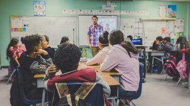Kinderen in de klas met een meester bij het bord die goed begeleid bij het van school veranderen van een van de kinderen