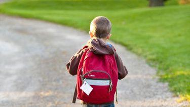 Jongetje dat naar de basisschool loopt