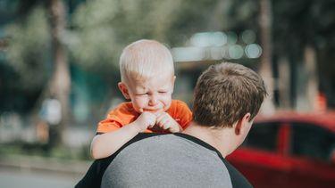 Vader die boos is op zijn kind en deze huilend draagt
