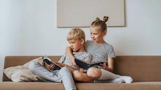 band tussen kinderen / broer en zus zitten te lezen op de bank