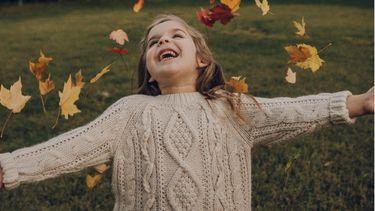 verlegen kind speelt met bladeren