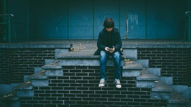 cyberpesten / kind zit op muurtje met telefoon
