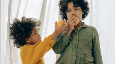 rekening houden met anderen / twee kindjes eten fruit